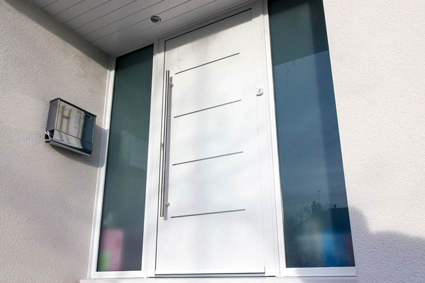 Aluminium entrance door in white with stainless steel large handle.