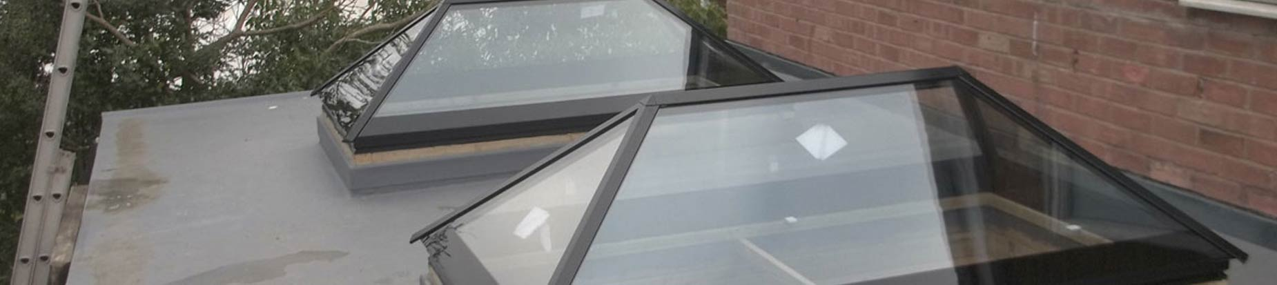 Dual glass roof lanterns installed on a flat fibrglass roof.