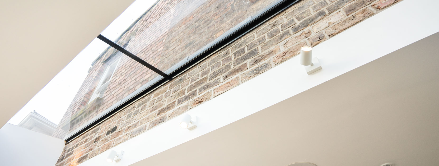 Bespoke glass roof light connecting the existing building to the new extension in Liverpool. This stunning feature bridges the gap between modern and old in a seemingly impossible way leaving the main back wall of the house to appear as if it is floating in the air.