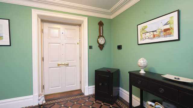 Internal view of this period home showing the white finish of the door internally with brass hardware and hinges.
