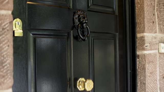 Close up of the brass hardware and black door knocker. Natural timber grain is showing through within the painted finish of the door.