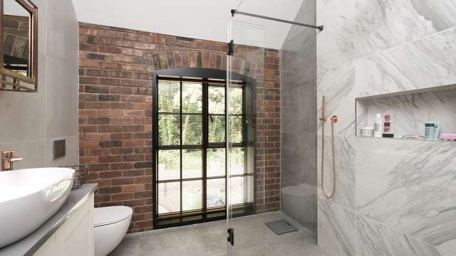 Bathroom fitted with large Crittall window.