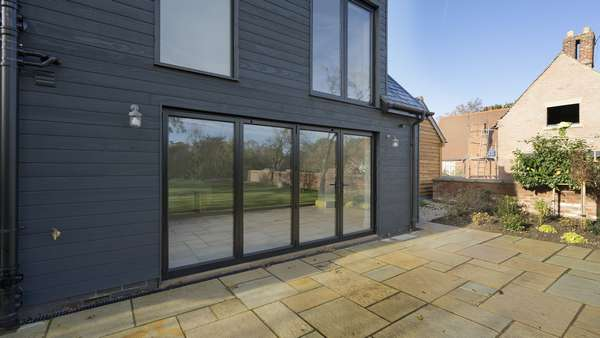 External view of the black aluminium bifolds installed in Cheshire.