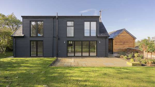 External view of the rear of the property showing all aluminium windows and doors in black.