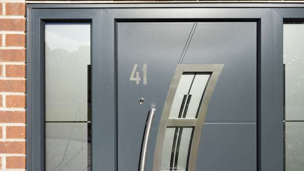 Close up of the stainless steel number and inset details on the grey aluminium front door.
