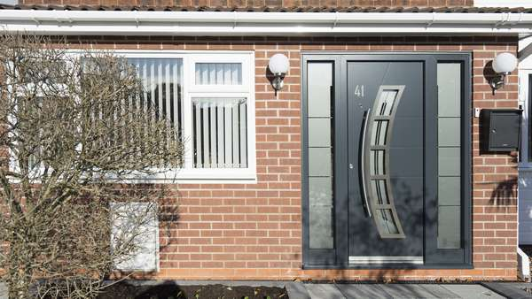 Straight on picture of the aluminium entrance door in anthracite grey with stainless steel accents and privacy glass.