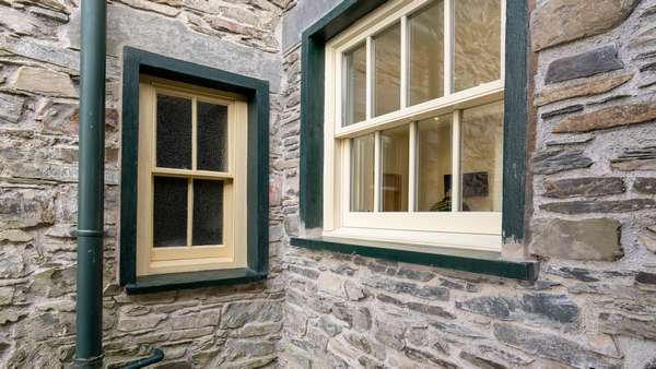 Showing the difference between the new and old, original timber sash window and larger new alu-clad sash window.