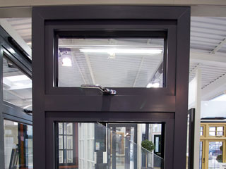Full height view of Aluminium triple glazed window with chrome finish handles.