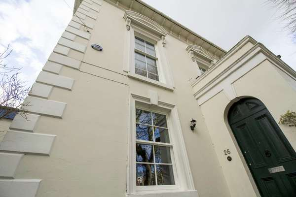 Close up of side entrance door showing newly installed sash windows.