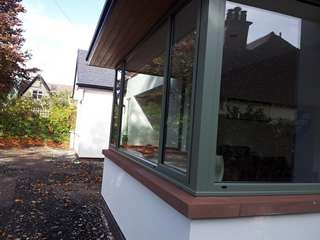 Close up showing green aluminium windows installed in new build property Caldy, Wirral.