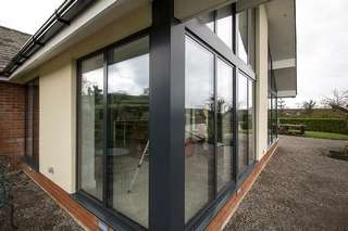 Extrernal view of large aluminium window installation in Ormskirk, Liverpool. Large windows and doors allow a large amount of light to enter this stunning open plan living area in Liverpool. Although large amounts of glass have been installed the use of triple glazing and thermally broken frames ensure this is a warm space useable year round. This picture highlights the aluminium pressings used on the corner to create a modern seamless look to this extension.