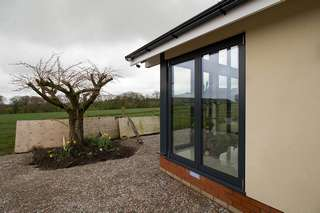 External corner view showing the aluminium Centor bifold doors in matching grey. The doors have are close in spec to the windows with triple glazing and grey aluminium thermally broken frames.