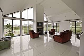 Internal view of modern open plan living space flooded with natural light from large aluminium glazing installation.