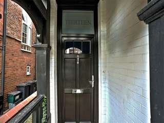 Black timber alternative entrance door with feature top lights with sand blasted lettering.
