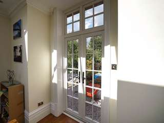 Internal view of Evolution timber alternative UPVC French doors with top lights and cast iron black door furniture.