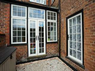 Traditional french doors with top and side lights with cast iron door hardware to match that of the original windows and doors.