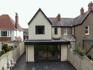 External shot of open plan extension with roof light and sliding door.