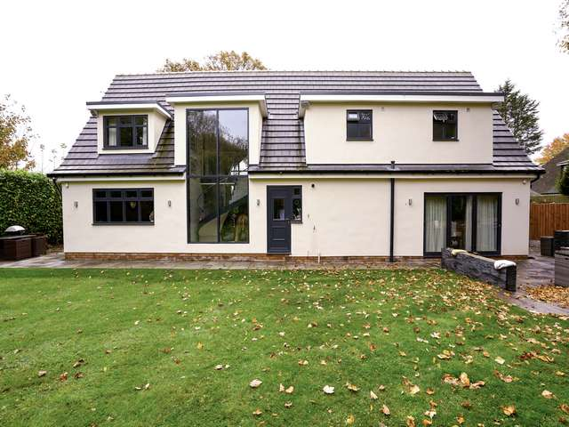 Rear view of property with feature curtain walling area, rear composite door, aluminium bifolds and various casement windows.