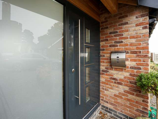 CLose up of aluminium entrance door and sidelight.
