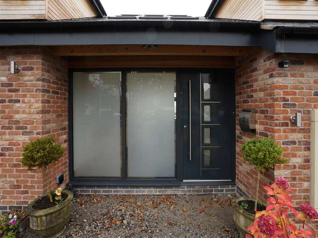 Aluminium entrance door with feature stainless steel handler and multipoint locking in RAL 7016.