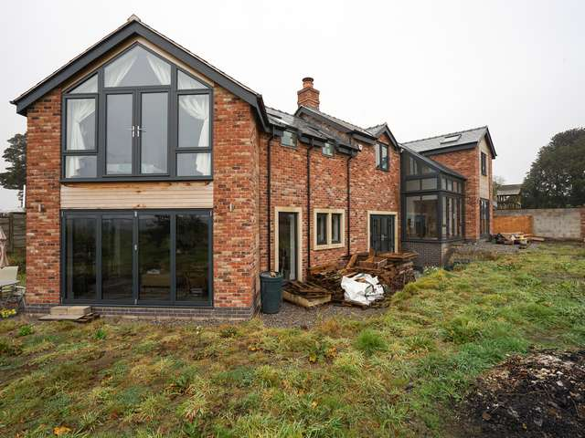 Rear of property showing bifold doors, and multiple sets of french doors as well as feature glass room.