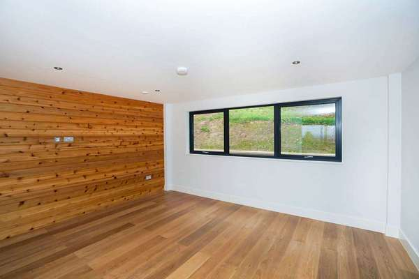 Internal living space with feature aluminium window and wood panelling.