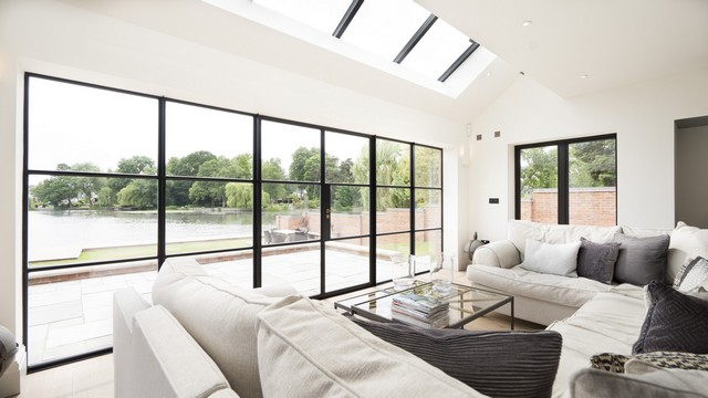 A bright living space making best use of the lake, viewed through a large set of Crittall doors, extra light added through the rooflight.
