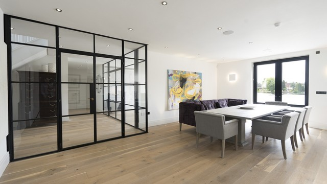 The dining area of this contemporary home showing the Crittall door and the lake through the aluminium french doors.