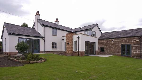The rear of the home looking its best, with the two differetn building styles and glazing schemes.
