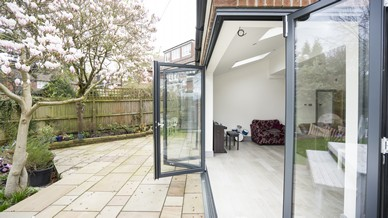 External shot of the RAL7016 aluminium bifolding doors showing the track and doors with the doors in an open position. The unique corner bifolding doors add the wow factor to any space with the floating corner of the building. Supplied and installed in Liverpool.