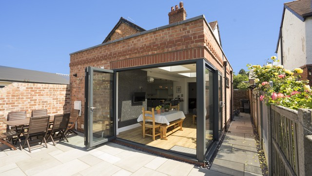 Brick extension with bifolding door in antracite grey opening outwards, with corner post and sliding door.