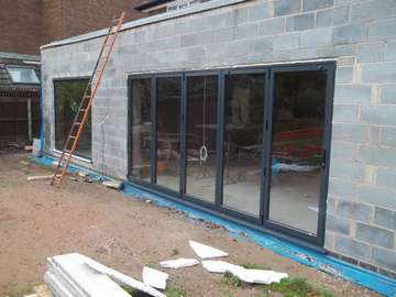 Installtion in Liverppool woolton area of our Allstyle Bi folding door system with a large Alstyle fixed window. the large panel is constructed of 8mm double glazed Toughned glass. low E soft coat glass. Argon gas filled
