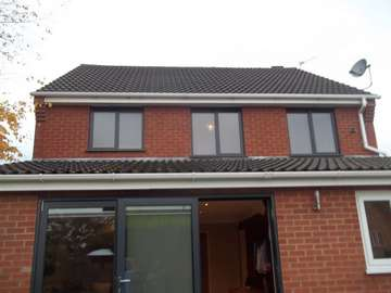 Rear elervation picture of a replacement installtion from PvcU white windows to 7016 grey Alumninium windows