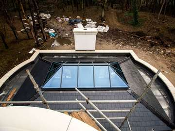 Grey aluminium roof lanterns in the centre of this double hipped roof maximising on light and making for a stunning design feature.
