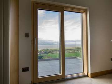 Internal view of Internorm lift and slide Alu-clad timber door, a great way to capture the view from the main bedroom and also gives access to the balcony.