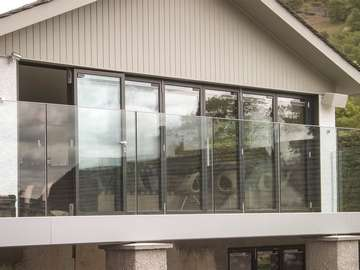 Large Aluminium bifold doors in RAL 7016 grey fitted with integrated blinds. The doors are made up of 7 individual panels create a large opening onto the customers balcony with feature glass balustrade.