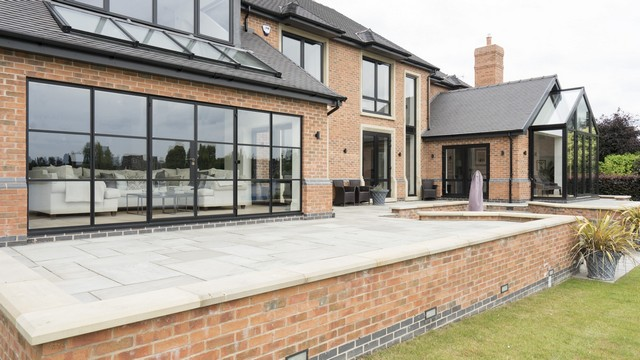 Angled view of the home highlighting the stunning glazed area, Crittall doors and various aluminium windows.