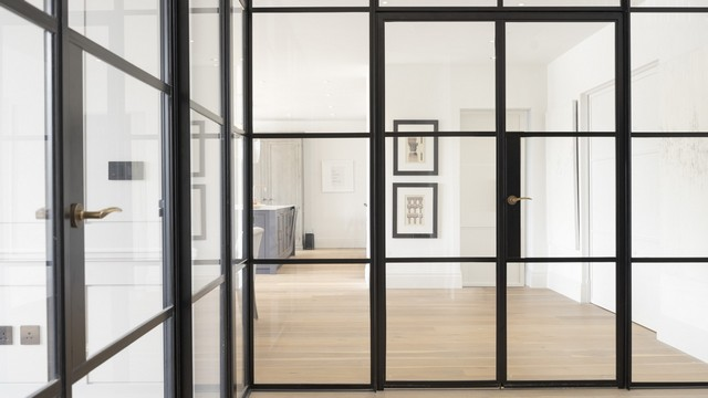 Close up of a dual Internal Crittall screen creating an L shape glass wall adding separation to this open plan home.