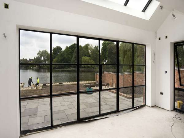 Internal view of large Crittall screen in black with opening doors and sidelights.