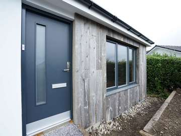 Rationel modern entrance door with matching grey colour to windows installed throughout this home.