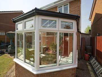 Replacement conservatory featuring a two tone colour scheme black roof with white windows giving a modern look. All glass is double glazed with a warm edge spacer for enhanced energy efficiency.