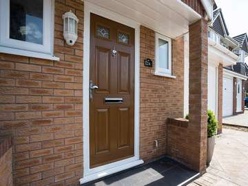 Brown wood effect composite entrance door installed in Great Sutton, Ellesmere Port. The door features lead light glazing, chrome door furniture and a white UPVC frame.