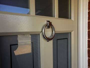 Feature door knocker in chrome.