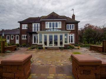 Straight on view of dual colour conservatory featuring Evolution windows.