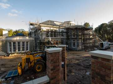 External shot of Formby mansion showing large glass installation nearing completion.