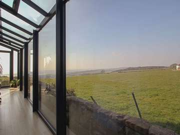 Making the most of the view from this bespoke aluminium gallery.