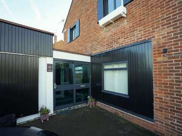 Sliding entrance door in Grey aluminium to match all windows installed throughout this installation.