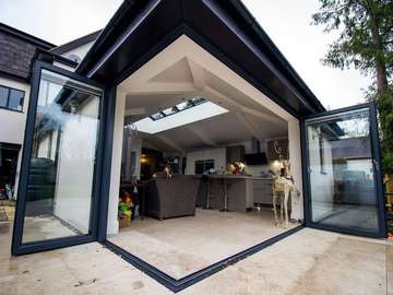 Open view of corner aluinium bifold doors showing the flush floor threshold for the perfect flow between the indoor and outdoor space, great for summer evenings and entertaining.