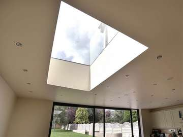 Insternal view of modern flat rooflight bringing in extra light to an otherwise dark space. Roof light is triple glazed with a U-value of 0.6 .