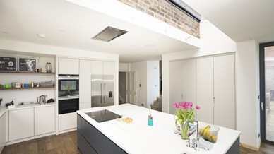 Overview of this stunning family kitchen space showing how the rooflight connects the new extension to the original building, this detail makes the back wall of the original house look as if it is floating freely above the kitchen island. A stunning detail that certainly adds the wow factor.